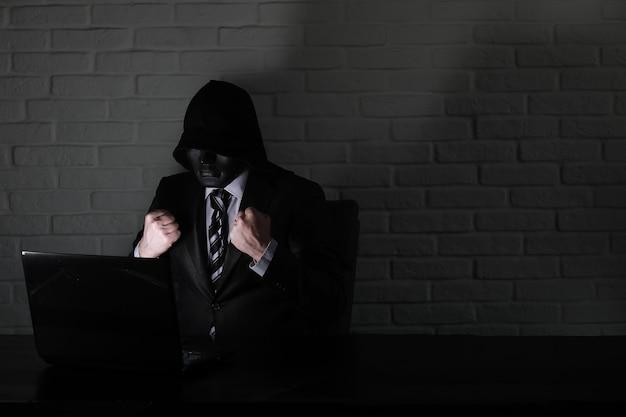 モニターの前のテーブルで黒いマスクとフードのハッカー