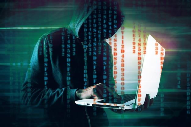 Хакер в капюшоне держит ноутбук