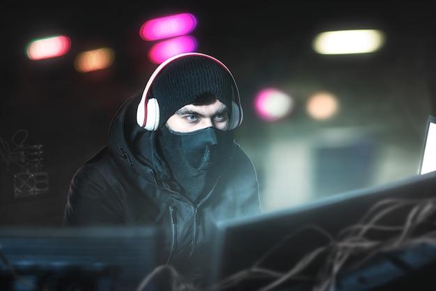 獲物を探してマイク付きのヘッドフォンを持ってオフィスにいるハッカー。彼の地下の隠れ家から銀行のデータとコピーを盗む