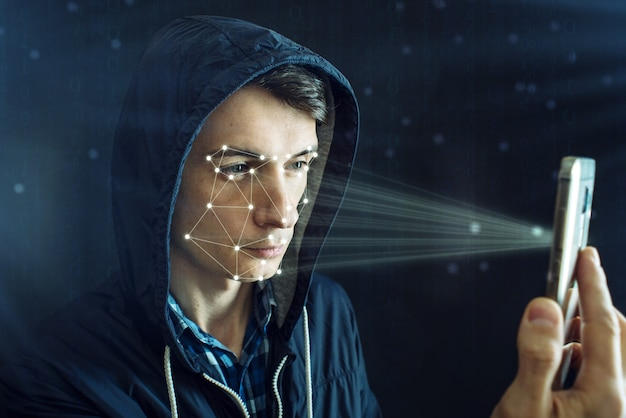 Хакер пытается взломать телефон, используя личный идентификационный метод распознавания лиц.