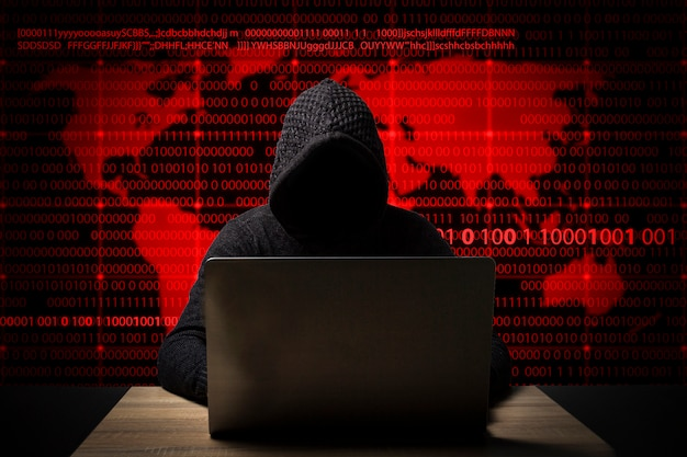 Hacker in a jacket with a hood with a laptop sits at the table. added identity theft icons, account hijacking, bank data theft and world map