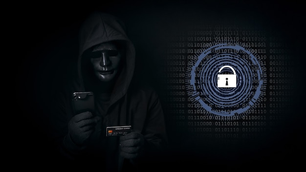 Hacker man in hooded and mask use smartphone and credit card, break security data and hack password with key unlocked.