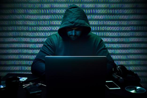 Hacker programmer using computer in dark room