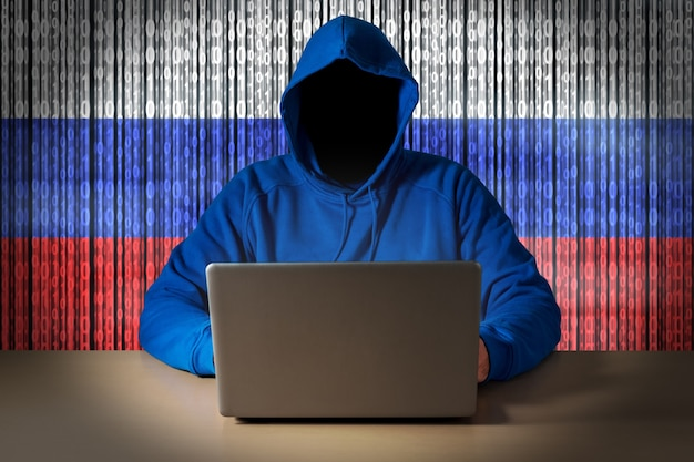 Hacker sitting in front of a laptop on background of digital flag of russia cyber