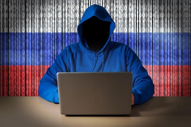러시아 사이버의 디지털 깃발의 배경에 노트북 앞에 앉아 해커