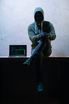 Hacker sitting next to laptop