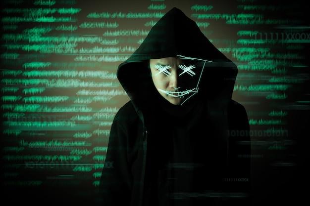 暗闇の中でハッカーが立っています。サイバー犯罪の概念。