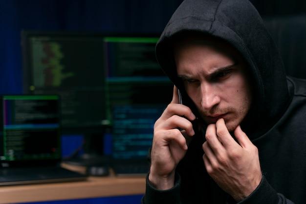 Хакер разговаривает по телефону крупным планом