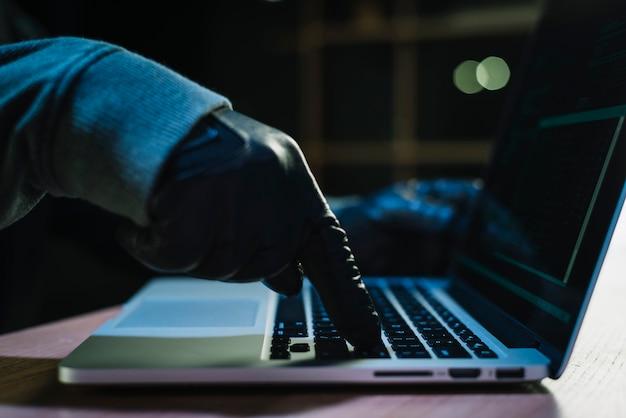 Hacker typing on laptop