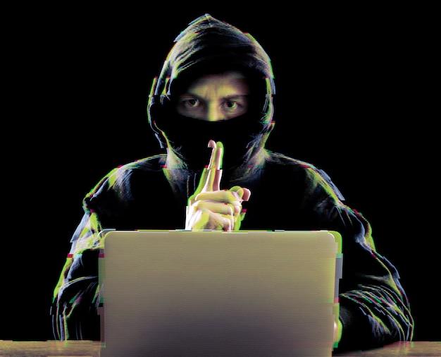 ラップトップを使用して企業サーバーで攻撃を仕掛けるハッカー