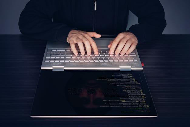 Хакер, использующий ноутбук. много цифр на экране компьютера. современный тонкий ультрабук-трансформер на столе. программный код амер, программный код, программный код.