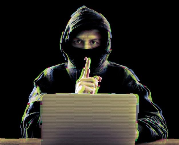 Hacker using laptop for organizing attack on corporate servers