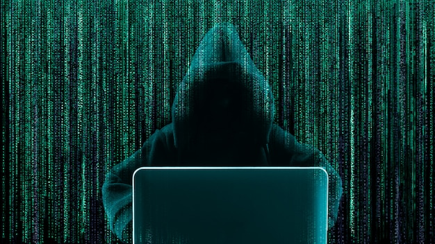 Hacker using laptop with abstract skull shape binary code.