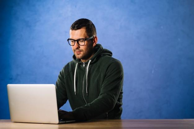 Хакер в очках, глядя на ноутбук
