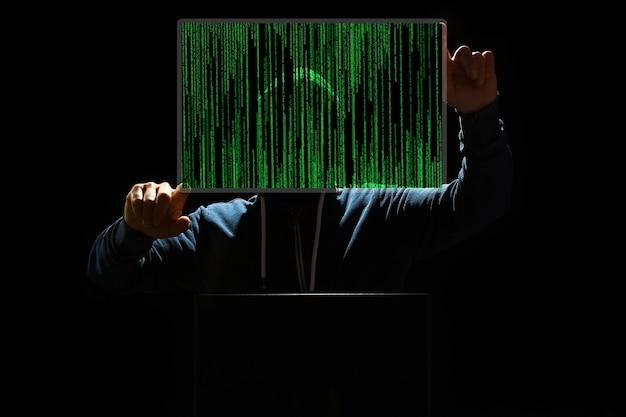 Хакер с ноутбуком и абстрактным двоичным кодом.