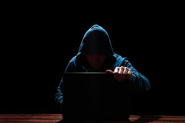 Hacker with laptop on black background