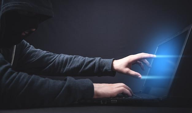 Хакер с ноутбуком. компьютерное преступление