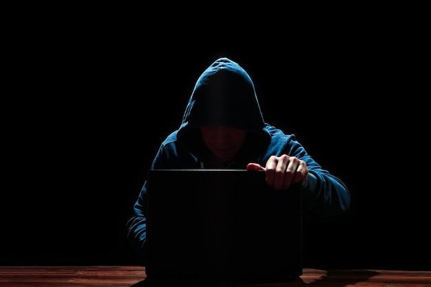 Хакер с ноутбуком на черном фоне
