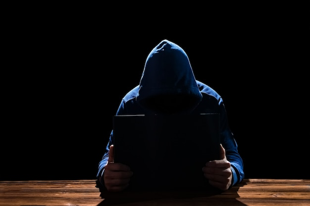 A hacker with laptop sits at a table and abstract binary code. business life threat virtual programs.