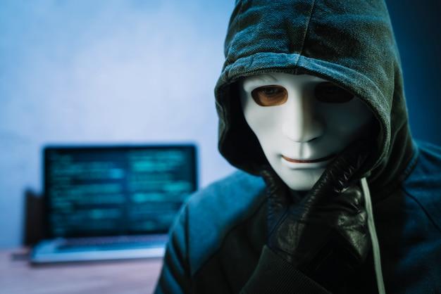ラップトップの前でマスクを持つハッカー