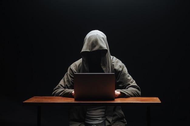 Хакер без лица в капюшоне с ноутбуком на черном фоне