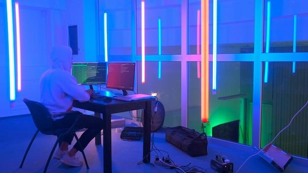 Хакер на рабочем месте хакер работает в комнате с цветными неоновыми огнями