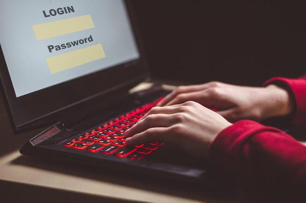 ハッカーは動作し、個人データに侵入し、ラップトップを使用してシステムにウイルスを感染させます。ハッカー攻撃、サイバーセキュリティ。ハッキングと個人情報の盗難、詐欺、詐欺の概念
