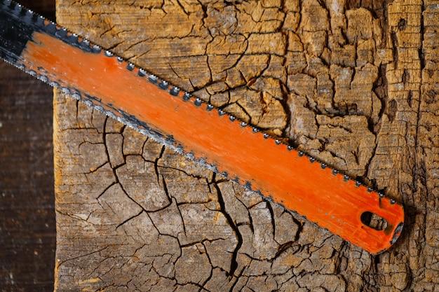 Hacksaw blade on wooden background