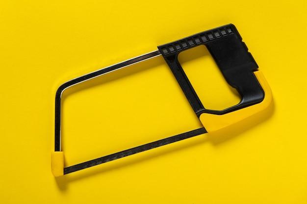黄色の背景に金属の弓のこ。配管や建設を修理するために職人によって適用されます