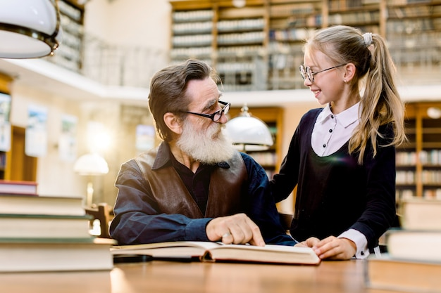 Hadsome bearded senior man grandfather and little cute granddaughter reading books together, smiling and looking each other, while sitting in old vintage library