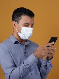 Красивый мужчина в синей рубашке в маске с мобильным телефоном в руках на желтом фоне