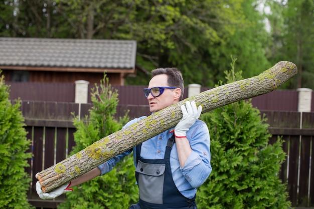 作業服を着たハンサムな男性の木こりが鋸で挽かれた木の幹を肩に運ぶ