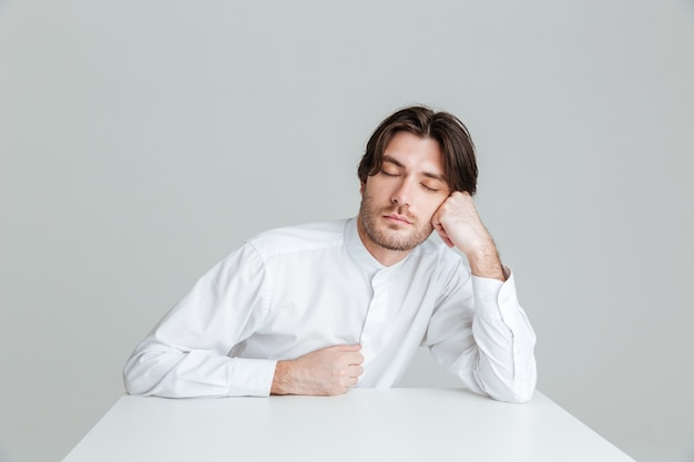 회색 벽에 격리된 책상에 앉아 있는 동안 흰 셔츠를 입은 멋진 청년