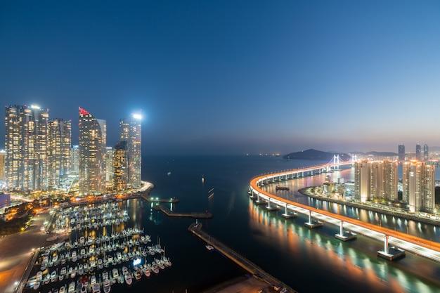 Горизонт города пусана в взгляде горизонта района финансового района haeundae от верхней части крыши на ноче в пусане, южной корее. азиатский туризм, современная городская жизнь или бизнес финансы и концепция экономики