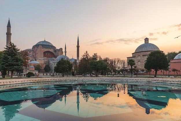 アヤソフィアまたはアヤソフィアのモスク博物館と噴水、トルコのイスタンブールにあるスルタンアフメット公園からの日の出の景色を映し出す