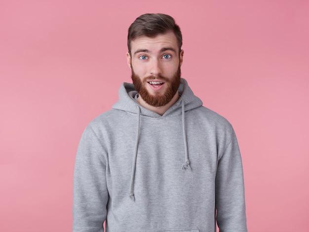 Ah, davvero? il giovane uomo barbuto rosso bello in felpa con cappuccio grigia sembra sorpreso, si trova su sfondo rosa guarda la telecamera con stupito.
