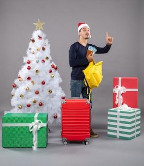 サンタの帽子と赤いスーツケースを持った若い男を呼んで、灰色のさまざまなプレゼントの周りに黄色のバックパックをチェックします