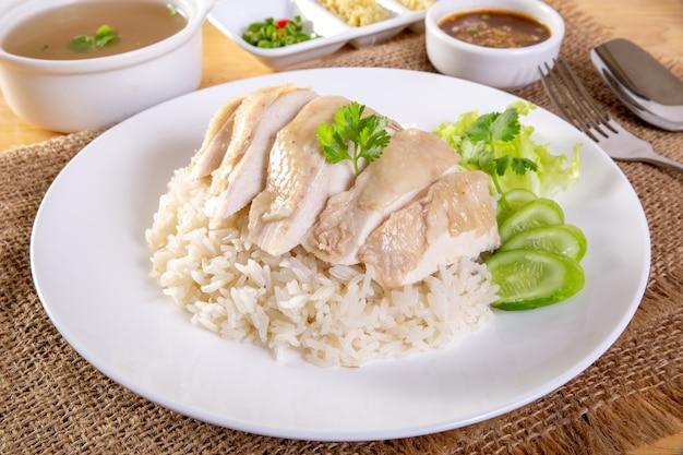 木製のテーブルの上の海南のゆでた鶏の米