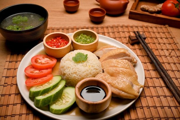海南チキンライスは、テーブルの上にチキンスープまたはスープと箸を添えて提供されます