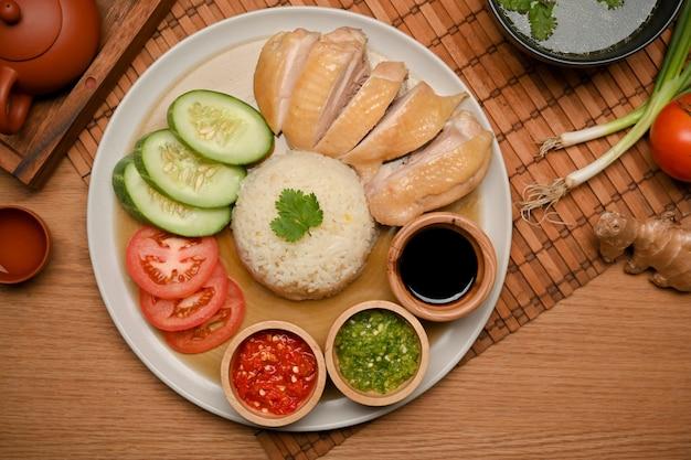 Курица с рисом по-хайнаньски или курица на пару с приправленным рисом с соусами чили и сладким соевым соусом