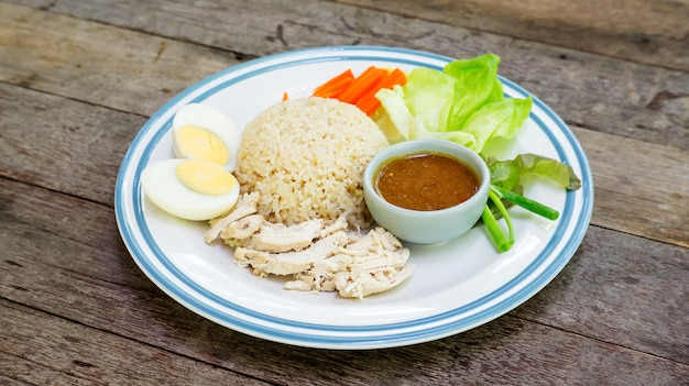 Hainanese chicken rice with boiled egg on a wooden table.