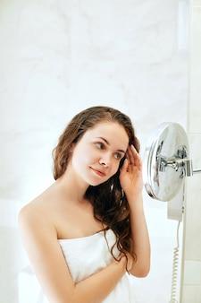 Уход за волосами и телом. женщина трогательно волос и улыбается, глядя в зеркало. портрет счастливой девушки с мокрыми волосами в ванной комнате, применяя кондиционер и масло.