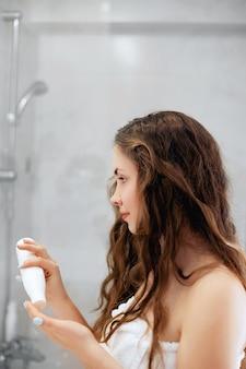 헤어 및 바디 케어. 젖은 머리를 만지고 거울을 보면서 웃는 여자. 컨디셔너와 오일을 적용하는 욕실에서 여자의 초상화. 여성의 초상화는 보호 보습 크림을 사용합니다.