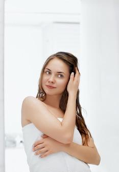 Уход за волосами и телом. женщина трогательно влажных волос и улыбается, глядя в зеркало. портрет девушки в ванной, применяя кондиционер и масло. женский портрет использует увлажняющий крем защиты.