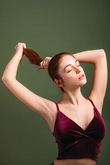 ヘアビューティーケア。ポニーテール。若い女性の赤毛の女性。腕を上げた。目を閉じて