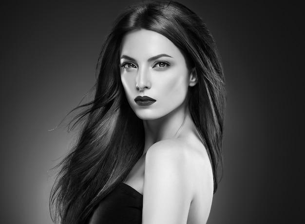 머리 아름다움 여자 긴 bruette 부드러운 아름 다운 매니큐어 손톱 모델 빨간 립스틱 갈색 배경 저녁 화장 초상화. 스튜디오 촬영. 회색. 단색화. 검정색과 흰색.