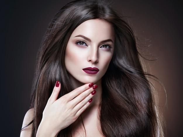 Волосы красота женщина длинные bruette гладкий красивый маникюр ногти модель красная помада коричневый фон вечерний макияж портрет. студийный снимок.