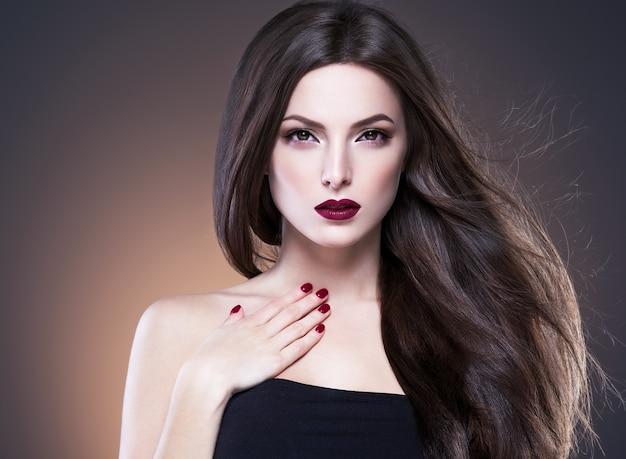 머리 아름다움 여자 긴 bruette 부드러운 아름 다운 매니큐어 손톱 모델 빨간 립스틱 갈색 배경 저녁 화장 초상화. 스튜디오 촬영.