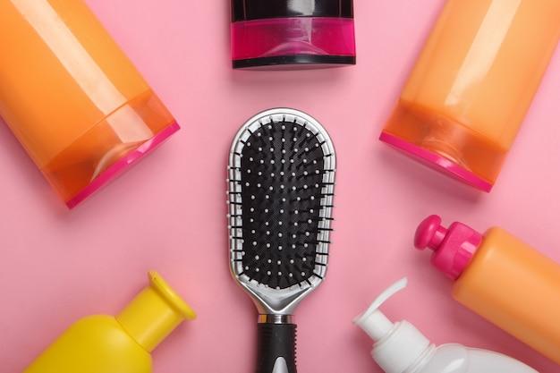 ピンクのパステルカラーのシャンプーボトル付きヘアブラシ。ヘアケア。衛生