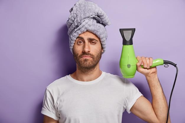 헤어 케어 및 손질 개념. 잠자는 남자가 헤어 드라이어를 들고 샤워 후 헤어 스타일을 만들고 머리에 부드러운 수건을 착용합니다.